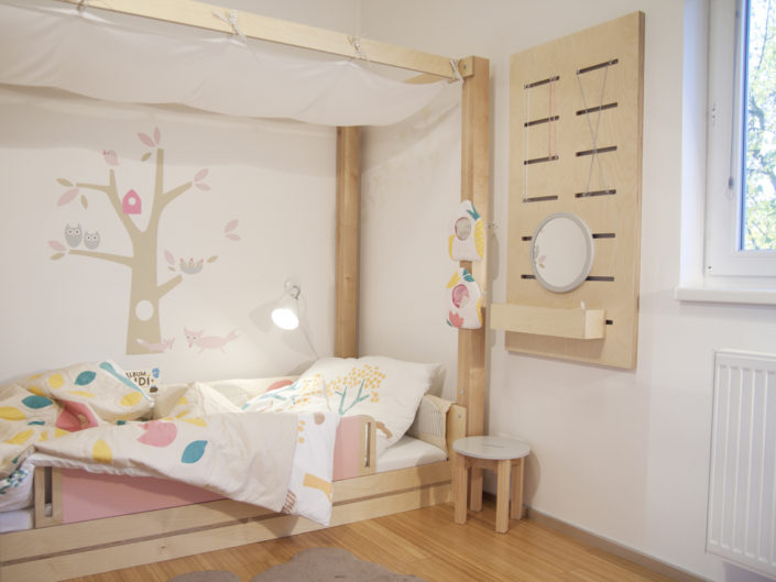 Světle hnědá postel s bílým sloním povlečením a garlandou