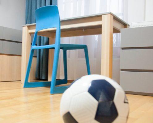 Psací stůl s modrou plastovou židlí