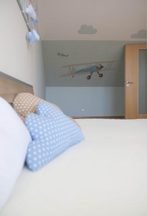 Modře vymalovaný pokoj s motivem letadla