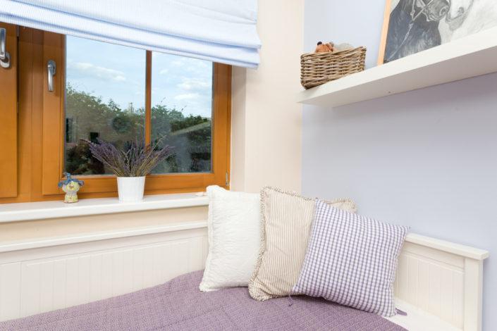 Bílá dřevěná postel s polštáři
