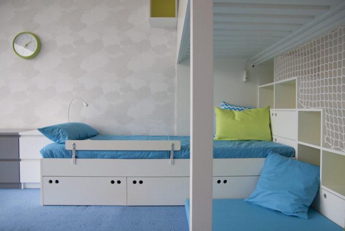 Prostorná postel s modrým povlečením a polštáři